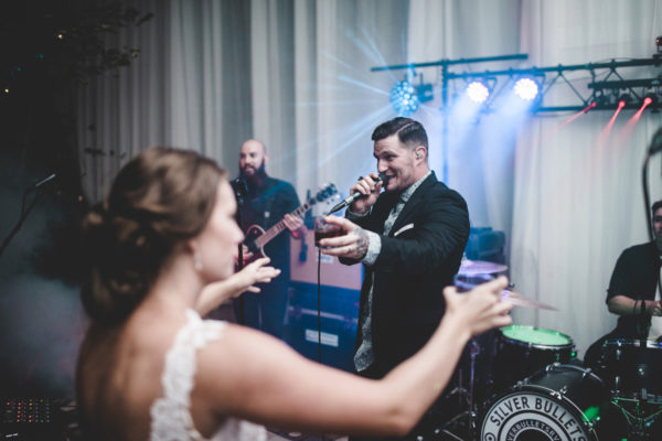 bride toasts with the band silver bullets at her wedding
